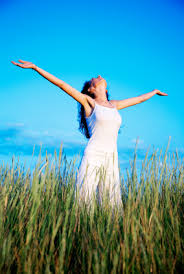 woman in field with arms outstretched in happiness